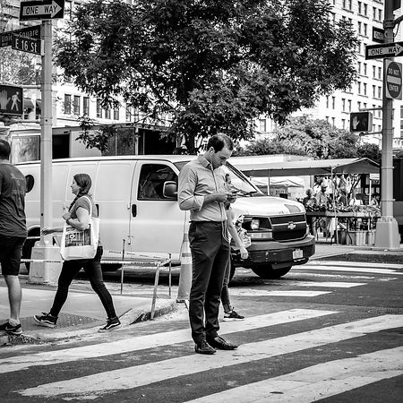Checking phone on street, New York