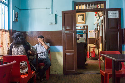 India - Kottayam - A man talks to a woman in the Indian Coffee House, Kottayam