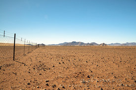 Barbed wire farm fence in a flat desert leading to a mountain range in the distance, barren, stony ground in the foreground