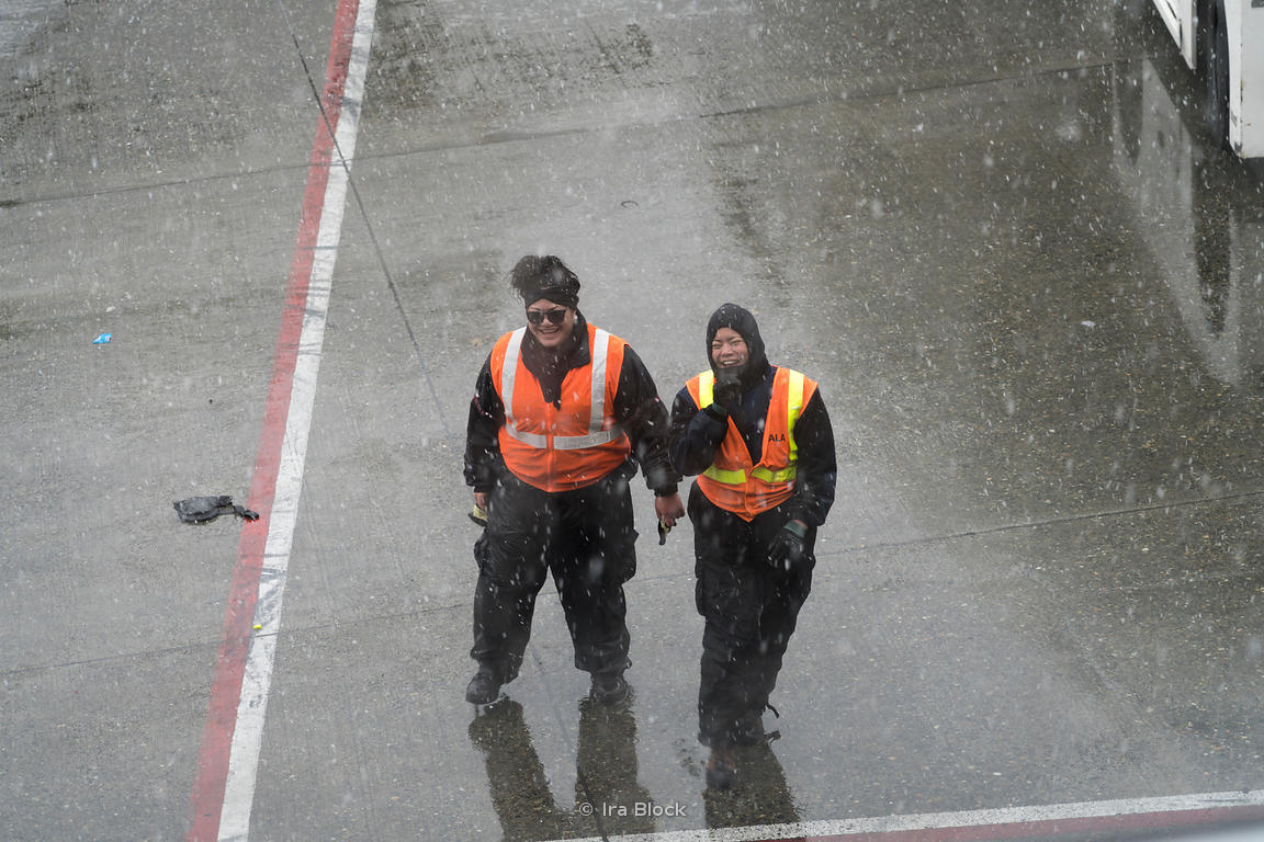 Workers at the Seattle - Tacoma international airport on a snowy day.