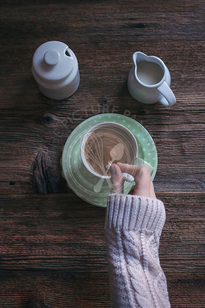 A womans hands stiring a cup of strong black coffee, with milk and sugar.