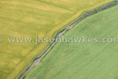 Narrow road through fields