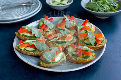 Chive Crostini with Cucumber, Roasted Red Pepper and Aruglua photographed from front view on a dark blue background.