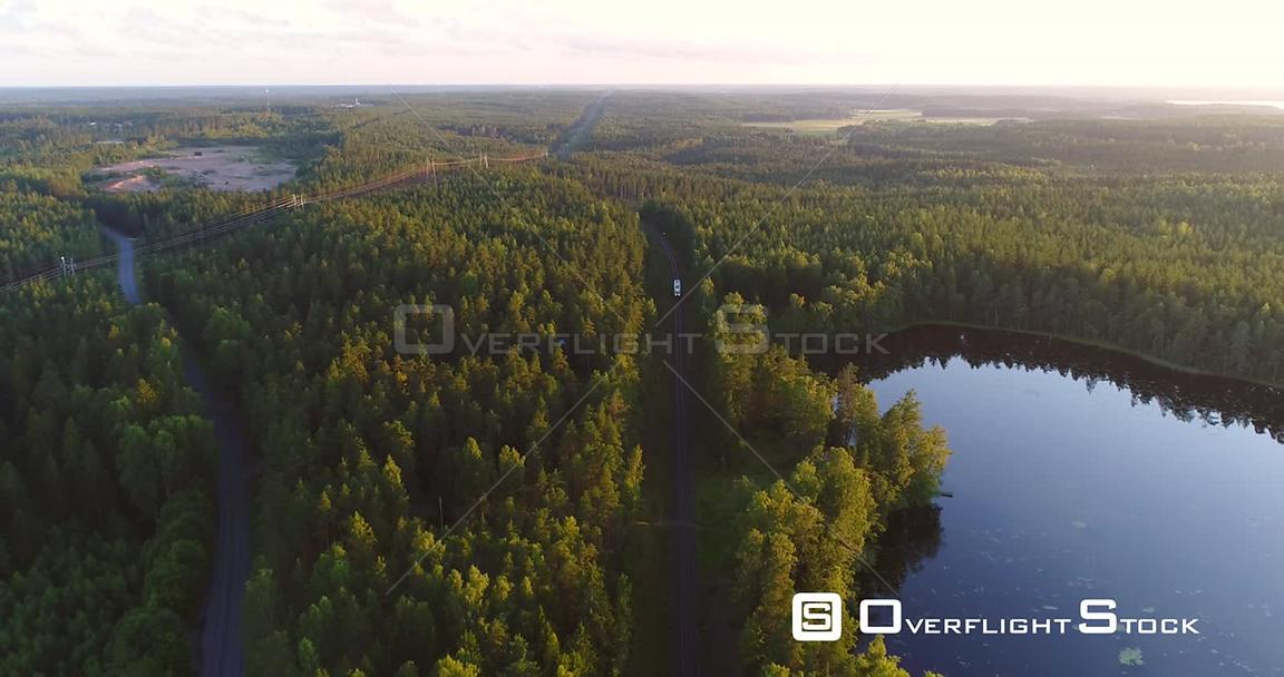 Train Passing by a Pond, Cinema 4k Aerial View Above Railway Tracks of a Little Train Bypassing a Reflecting Pond, on a Sunny Evening Dawn, on the Countryside, in Raasepori, Finland