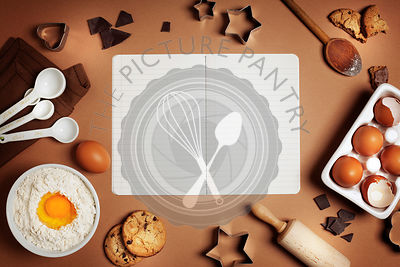 Baking background with ingredients for making chocolate chip cookies and recipe book. Top view. Flat lay style.