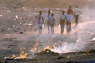 Women sweep up and burn garbage on a dusty desert road after the Pushkar Camel Fair, Pushkar, Rajasthan, India. Air pollution is an epidemic health crisis across India. India has the worst air pollution in the world, worse even than China, with Delhi the #1 worst city in the world.