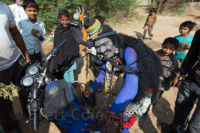A man dressed as Shiva works on his motorcycle before heading to Pushkar to have his picture taken by tourists on Mahashivaratri (Shiva's birthday), Doomara village, Rajasthan, India