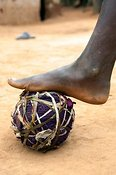 Children playing football with homemade ball.