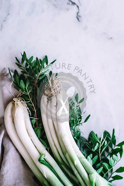 Fresh spring onions on a marble work surface