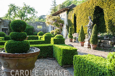 Box parterre with Casita beyond and Italian marble statue of youth against the yew hedge. Iford Manor, Bradford-on-Avon, Wiltshire