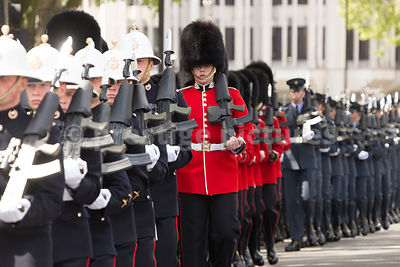 Scots Guards in their Red Tunics stand out against the dark Uniforms of the Royal Marines and RAF Airmen