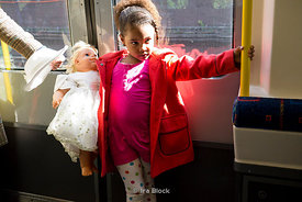 A girl holding a doll in a train of London Underground's Piccadilly Line, London, UK.