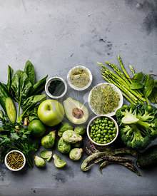 Healthy Green food Clean eating selection Protein source for vegetarians: avocado, asparagus, apple, broccoli, spinach, spirulina, green peas on gray concrete background copy space
