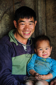 Hmong Man and Boy Sitting Outside Village Hut