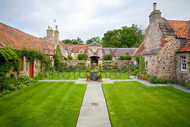 Lower courtyard featuring cruciform-paved path in lawn and edged with Digitalis, Salvia and Kirengeshoma