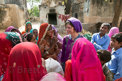 A female tourist from the UK talks to ladies in remote Nadi village, Rajasthan, India. Interesting to see how much more excited the women get to see a foreign woman visiting.