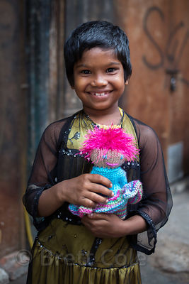 A girl from a low-income family with her doll in the Paharganj area of Delhi, India