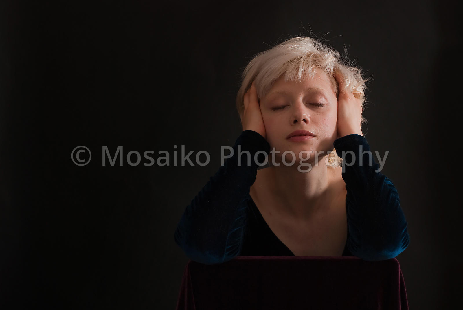 Young blond woman with closed eyes on black background - romantic portrait - studio shot
