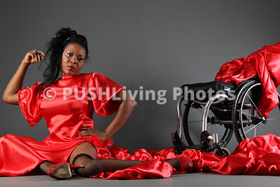 woman in long red dress sitting on floor next to wheelchair