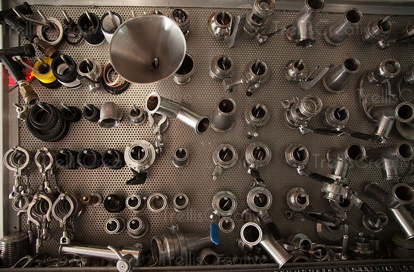 Stainless steel fittings and tools hang on a wall of a winery