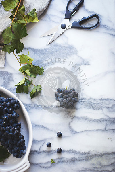 Black grapes on a marble surface