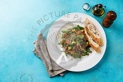 Salad with quinoa, tomato, avocado, spinach and arugula on white plate on blue background copy space