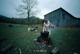 A woman on a farm cooking on an open fire in a cast iron pot.