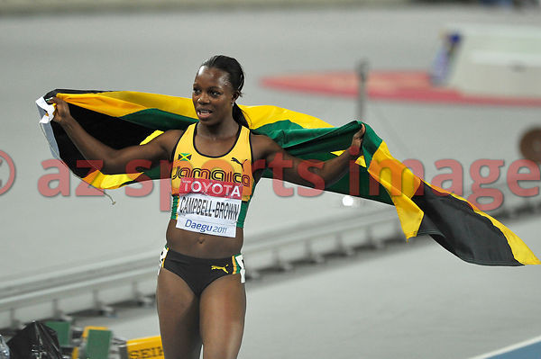 Veronica Cambell-Brown holds the Jamaican flag after winning the race.