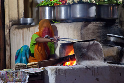 A woman cooks chapati bread over a primitive stove in Pushkar, Rajasthan, India