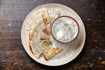 Yogurt dip with herbs Dzadziki cacik sauce and Pita bread on wooden background