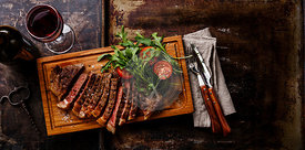 Sliced grilled beef barbecue Striploin steak and salad with tomatoes and arugula on cutting board on dark background copy space