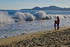 Waves crashing as father daughter watch