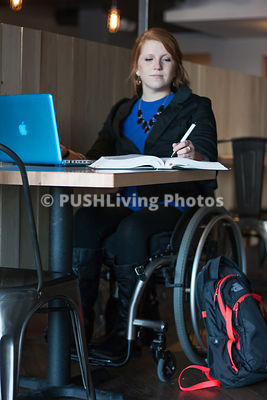 Young woman using a wheelchair studing on her laptop in a cafe