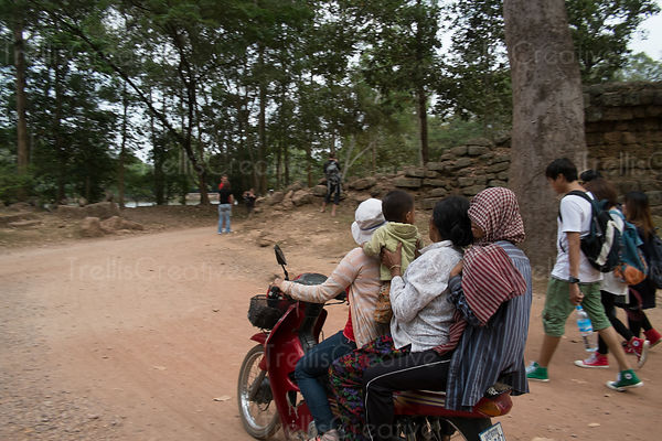 Women with baby riding on motorbike while tourist walk past