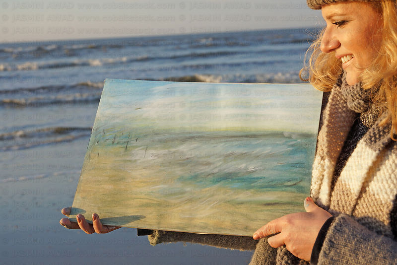 Artist at the beach with her freshly made oil crayon painting Evening light