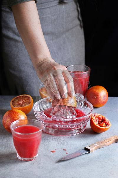 Female making blood orange juice with  a citrus hand squeezer