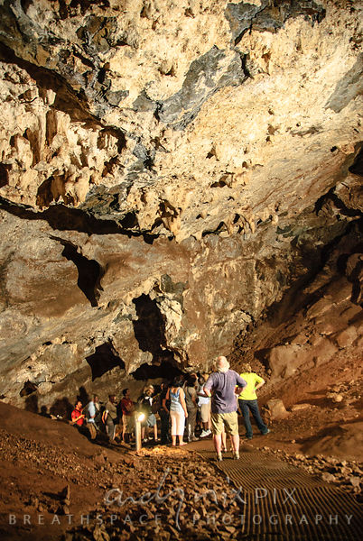 Sterkfontein Caves: A guide talking to a tour group in a cave filled with stalictites.