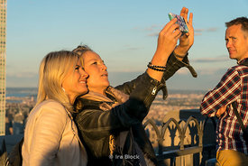 Tourists taking selfies on top of the Rockefeller Center in New York City.