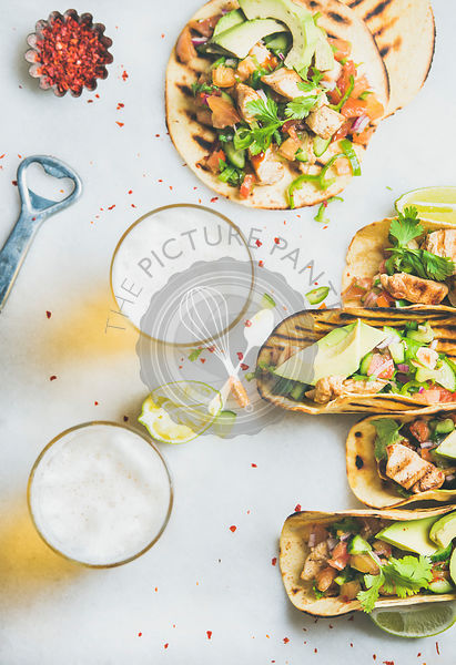 Healthy corn tortillas with grilled chicken, avocado, fresh salsa, limes, beer in glasses
