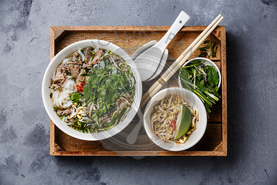 Pho Bo vietnamese Soup with beef in wooden tray on concrete background