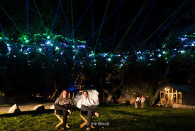 Two men watch a music concert and laser show in El Capitan in California.