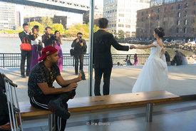 A bystander gazes as a wedding photoshoot happens at Brooklyn Bridge Park, New York.