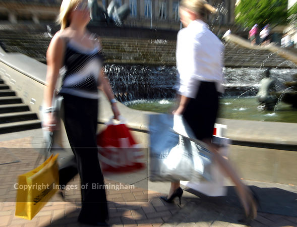 Action photo of women shoppers with carrier bags.