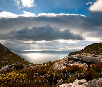 View of False Bay through a valley on a mountain, restios, rocks and fynbos in foreground, bright sunbeams shining through clouds on sea in distance