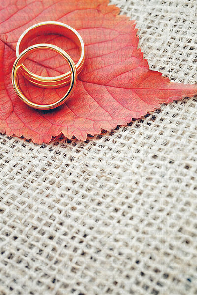Wedding rings with leaves on organic jute background and copy space