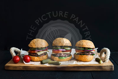 Fresh homemade burgers on wooden serving board over black  background.