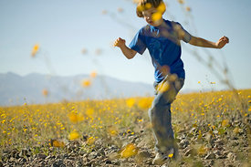 child playing in wildflowers in desert