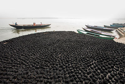 Animal dung (cow or water buffalo) patties dry on the ghats of Varanasi, India. They will be used for fuel for cooking and warmth.