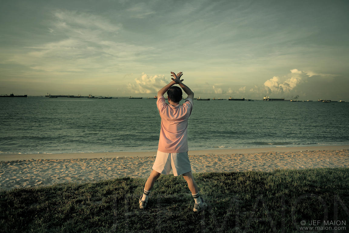 Man practising Tai-Chi on beach and cargo boats waiting to enter Singapore