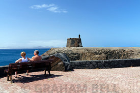 Couple sitting on bench with Castillo De Las Coloradas in the distance, Playa Blanca, Lanzarote, Spain.
